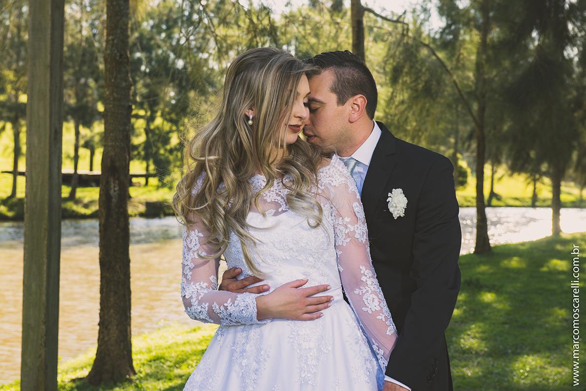 Noivo abraçando a noiva apoiando a cabeça no ombro da noiva em ensaio após o casamento. Foto por Marco Moscarelli