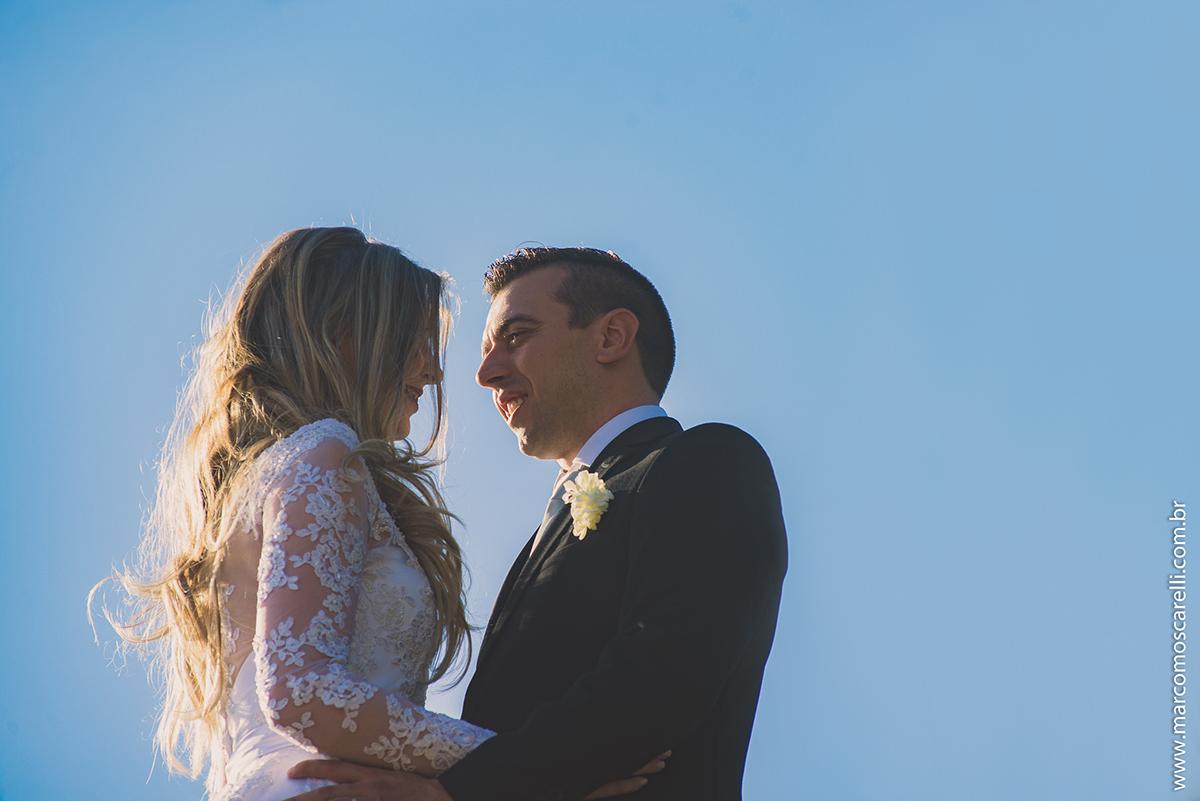 Foto contra a luzo do casael de noivos trocando olhares apaixonados com um lindo céu azul de fundo durante ensaio fotográfio após o casamento. Foto por Marco Moscarelli
