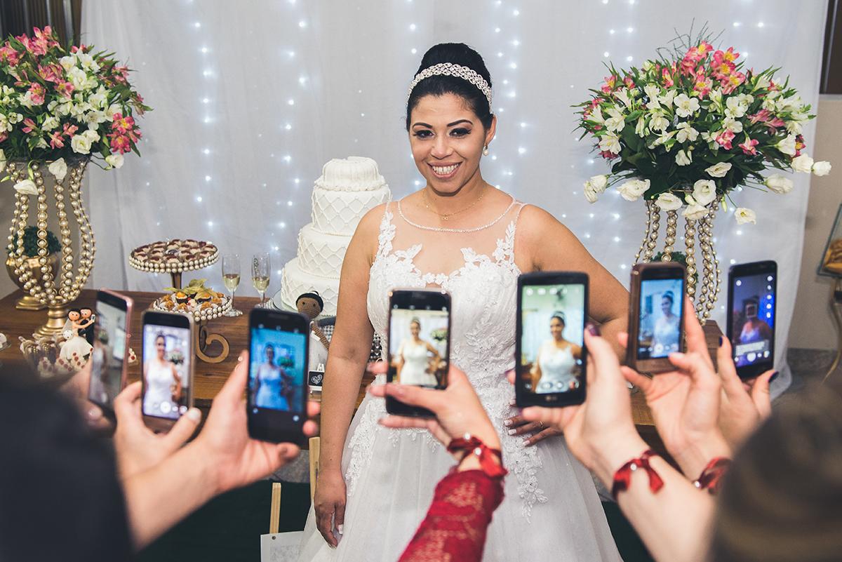 Foto divertida das madrinhas fotografando a noiva com os seus celulares.