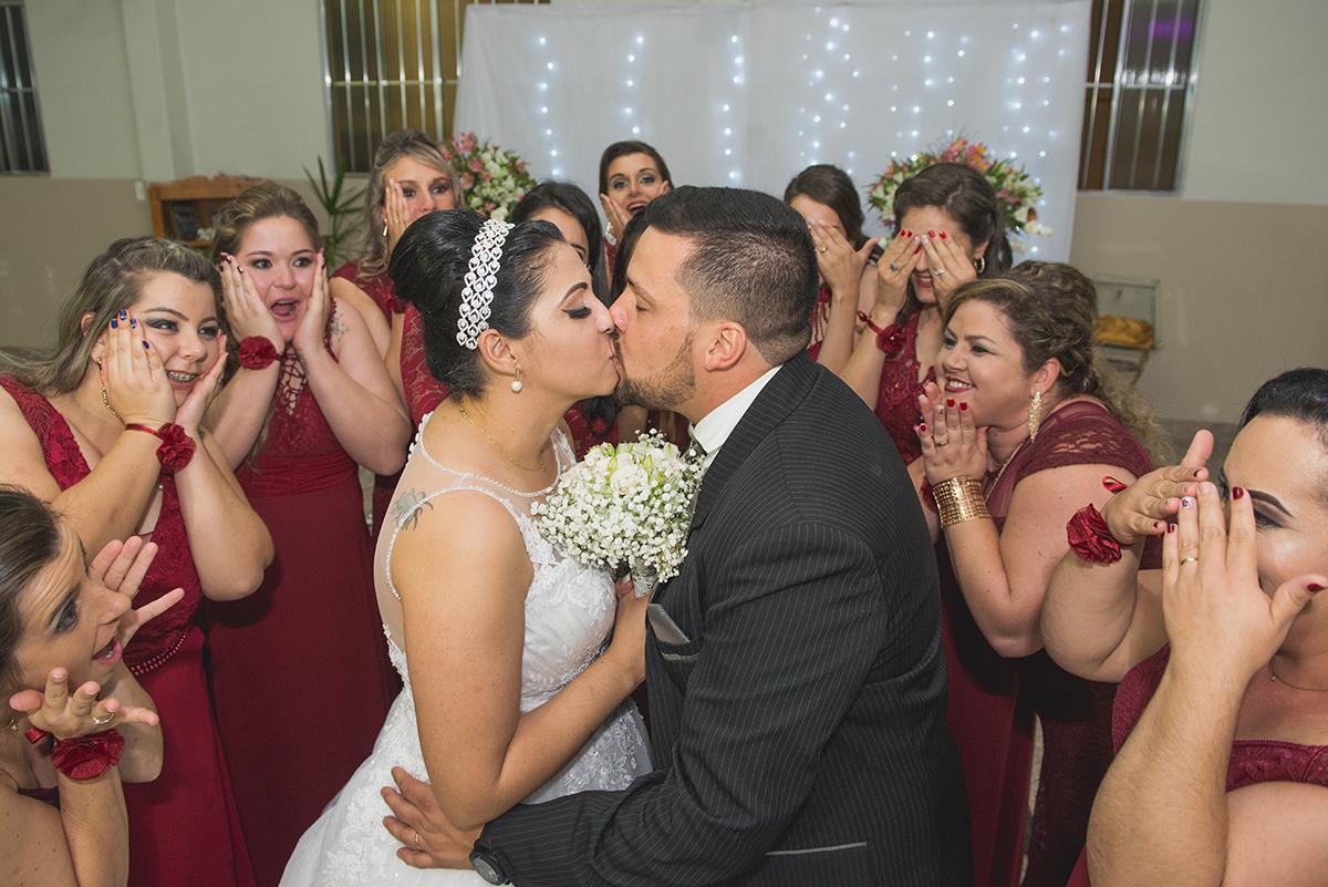 Casal de noivos trocando um beijo rodeados pelas madrinhas.