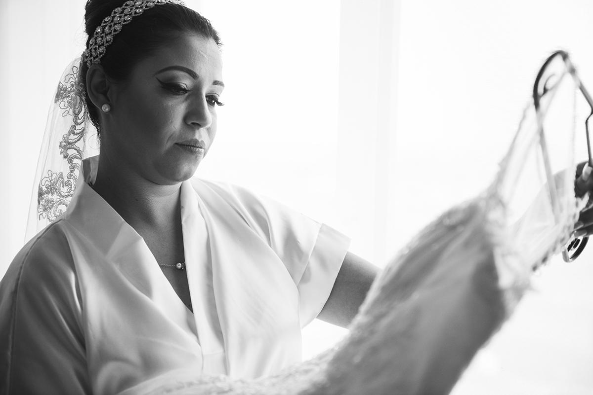Foto em preto e branco da noiva linda contemplando o seu vestido de noiva momentos antes da cerimonia de casamento