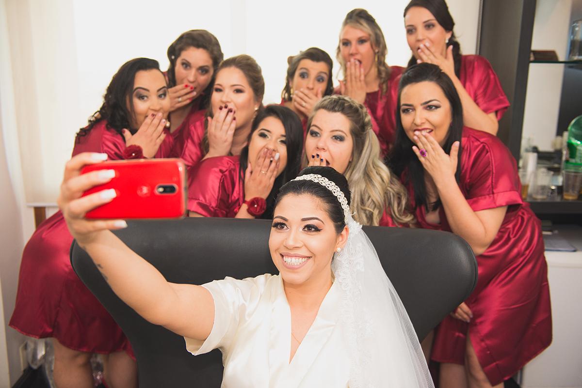 Foto bem humorada da noiva e das madrinhas do casamento posando para selfie.