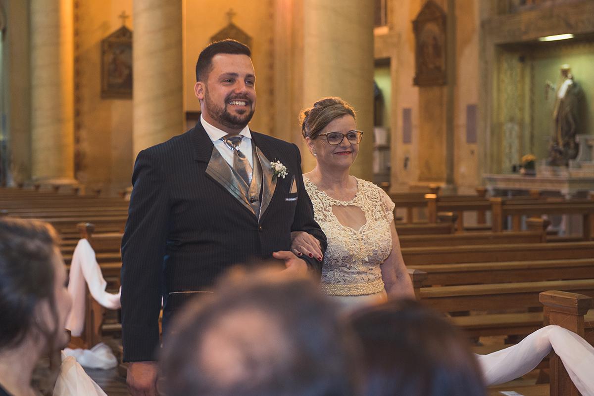 Noivo entrando na igreja com a sua mãe para a cerimonia de casamento.