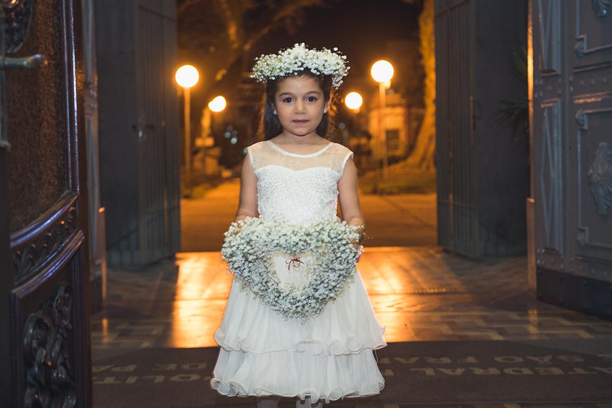 Aia entrando na igreja segurando um lindo arranjo de flores no dia do casamento.