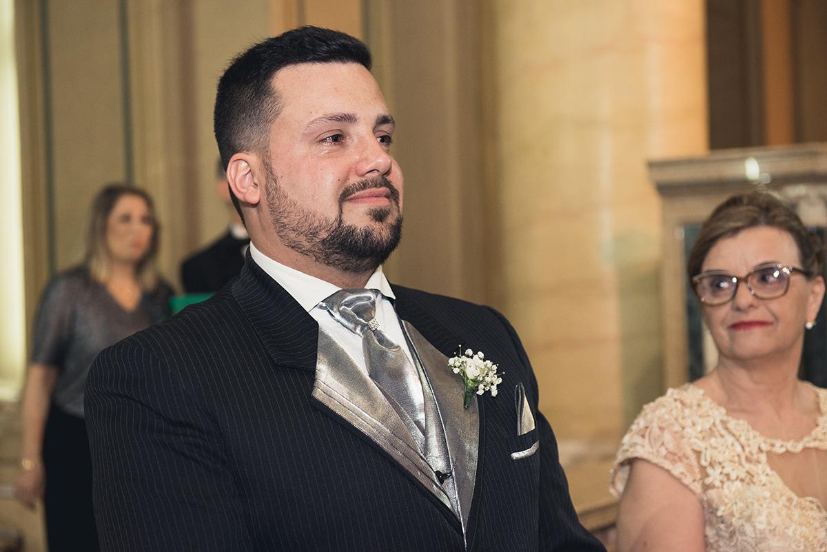 Linda foto em detalhe do noivo chorando quando visualiza a noiva chegado ao altar.