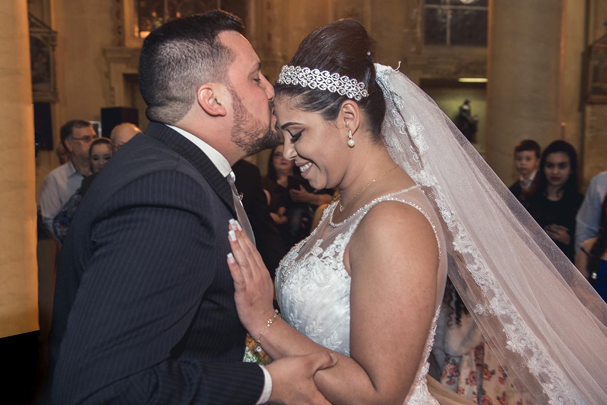 Detalhe do noivo beijando a testa da noiva no altar no dia do casamento.