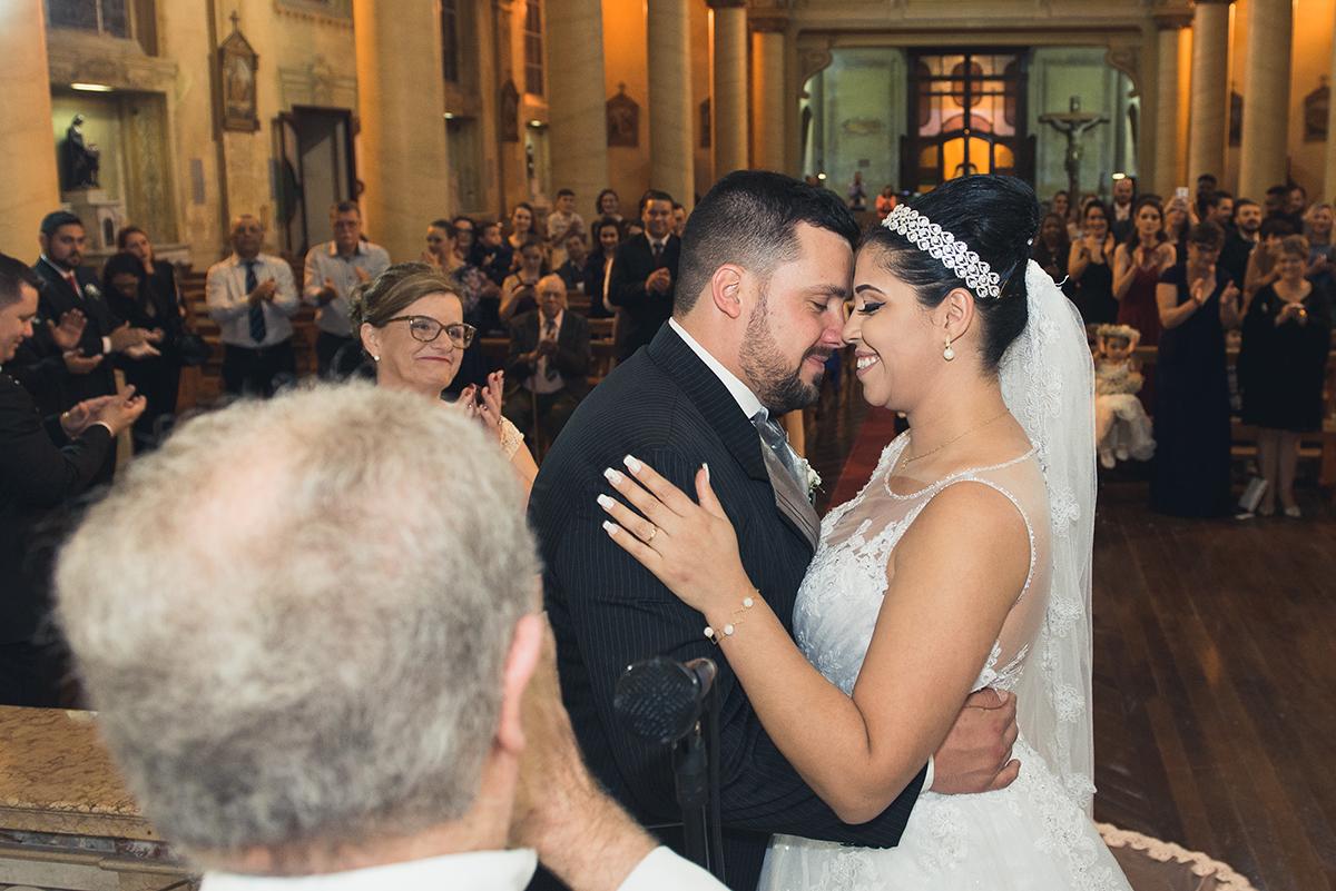 Noivos trocando umn  carinho com a testa durante a cerimonia de casamento.