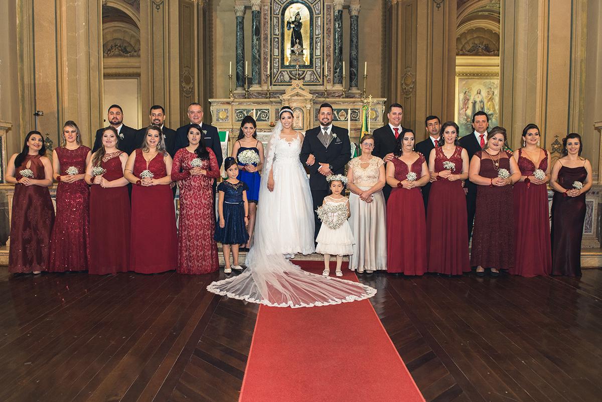 Fotografia oficial com padrinhos e familiares no altar ao final do casamento.
