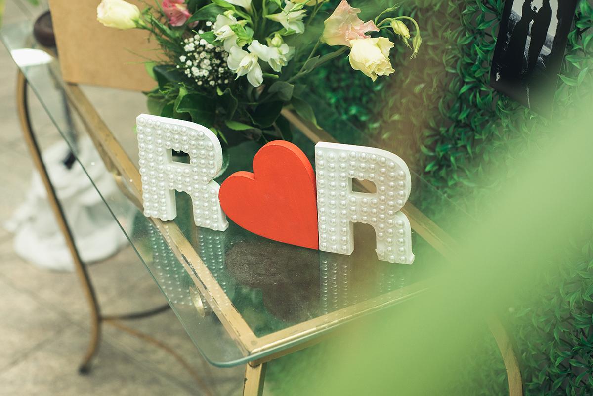 Detalhe da decoração da mesa da recepção dos noivos letras R e R, iniciais do casal.