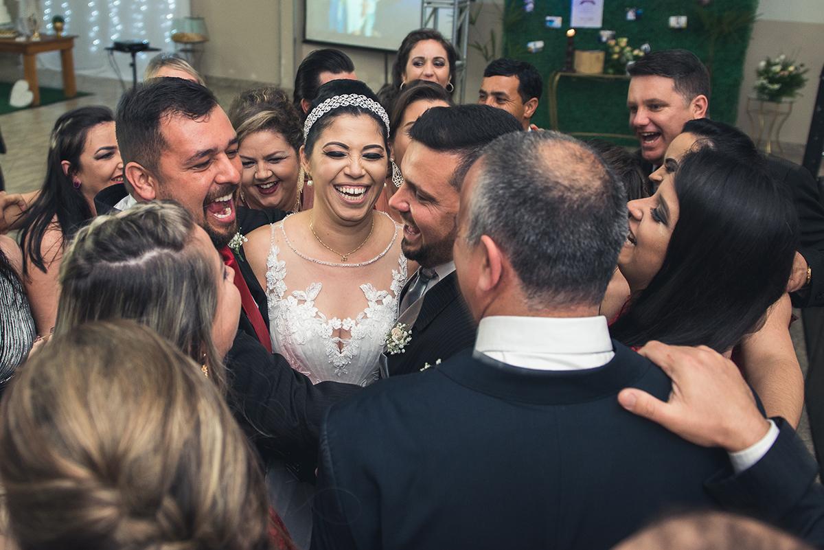 Foto dos padrinhos dos noivos todos em conjunto abraçando o casal durante a recepção do casamento.