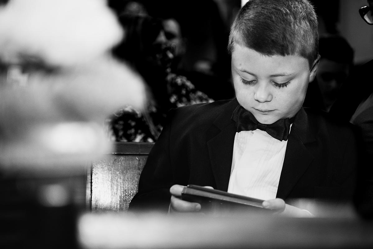 Detalhe durante o casamento do pequeno pagem brincando com o celular. Foto por Marco Moscarelli
