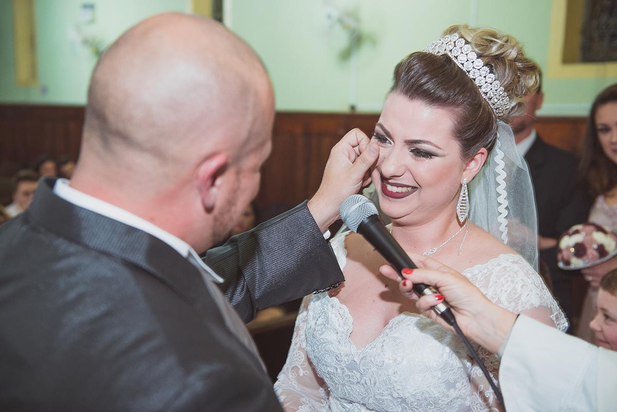 Noivo enchugando a lagrima do rosto da noiva durante a cerimonia de casamento. Foto por Marco Moscarelli