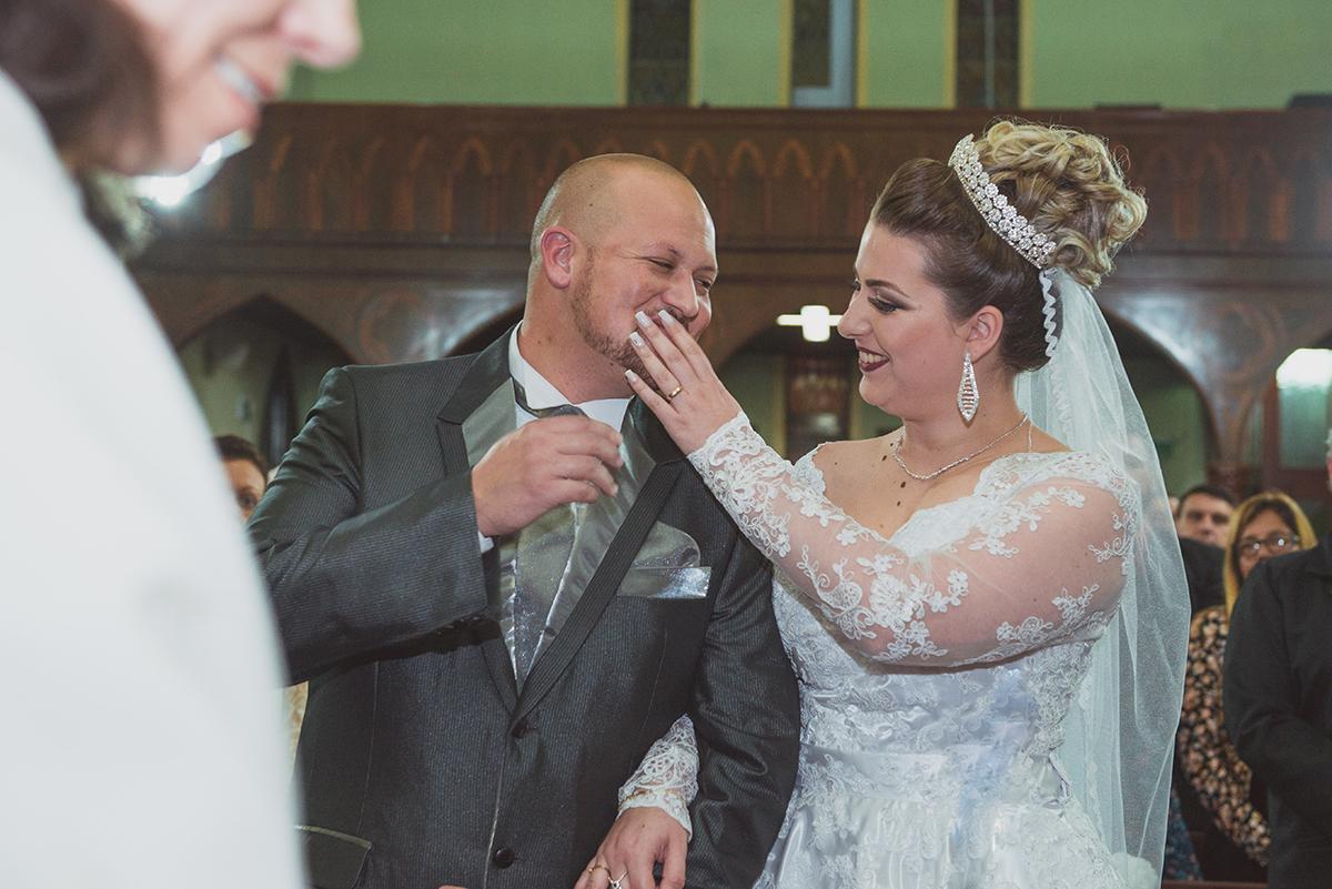 Noiva enchugando uma lagrima no rosto do noivo durante o casamento. Foto por Marco Moscarelli