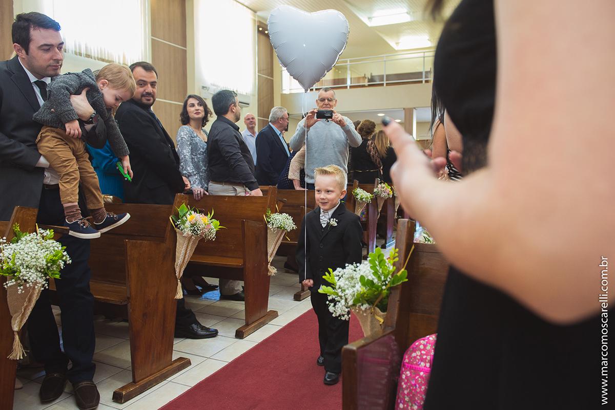 Entrada do pagem carregando um balão em forma de coração ma cerimonia de casamento. Foto por Marco Moscarelli