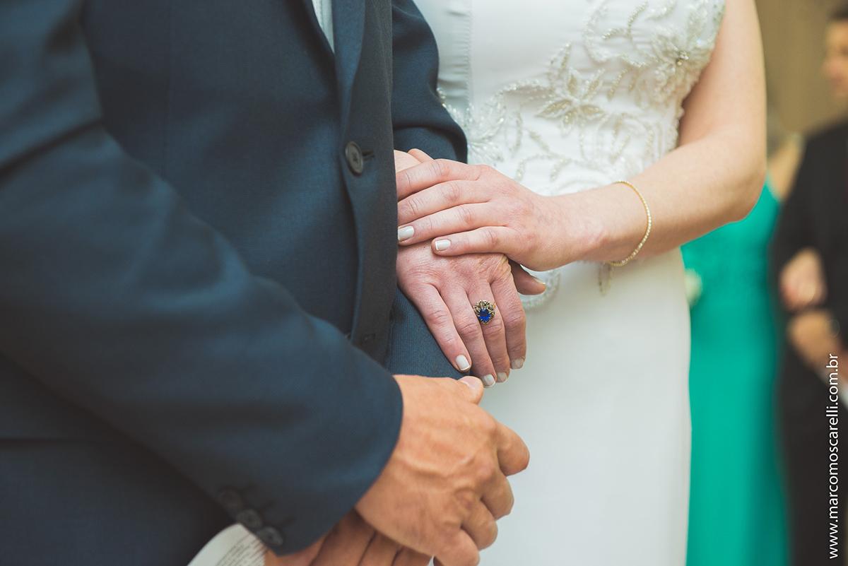 Detalhe da mão da noiva sobre a mão do noivo durante a ceromônia de casamento. Foto por Marco Moscarelli