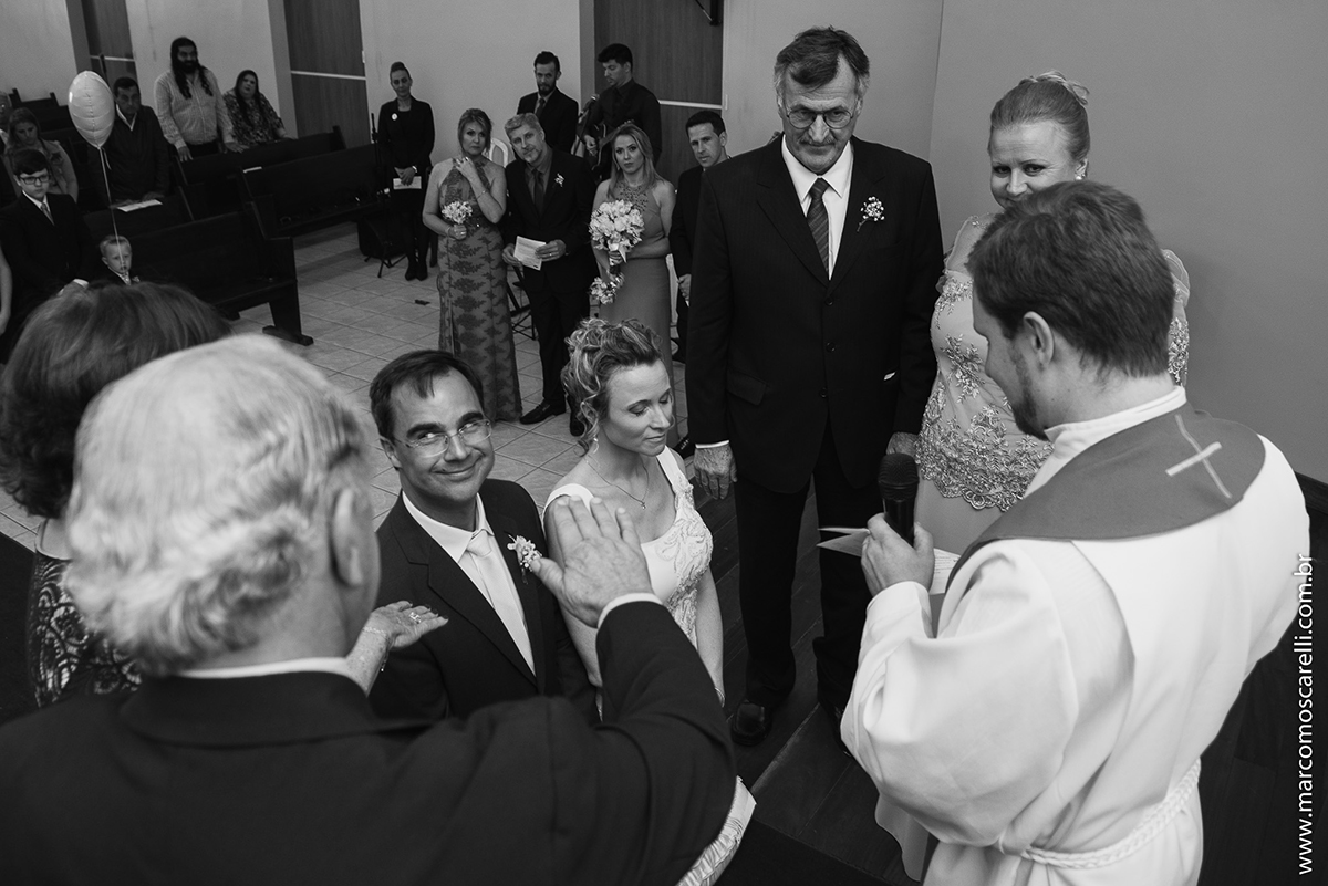 Foto em preto e branco dos noivos ajoelhados no altar da igreja e o noivo dando olhar engração para a sua ma. Foto por Marco Moscarelli