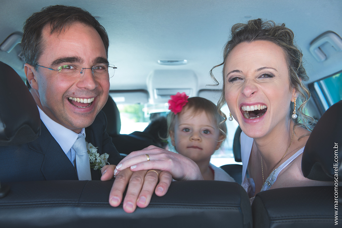 Foto descontraida dos noivos dentro do carro após a cerimônia de casamento. Foto por Marco Moscarelli