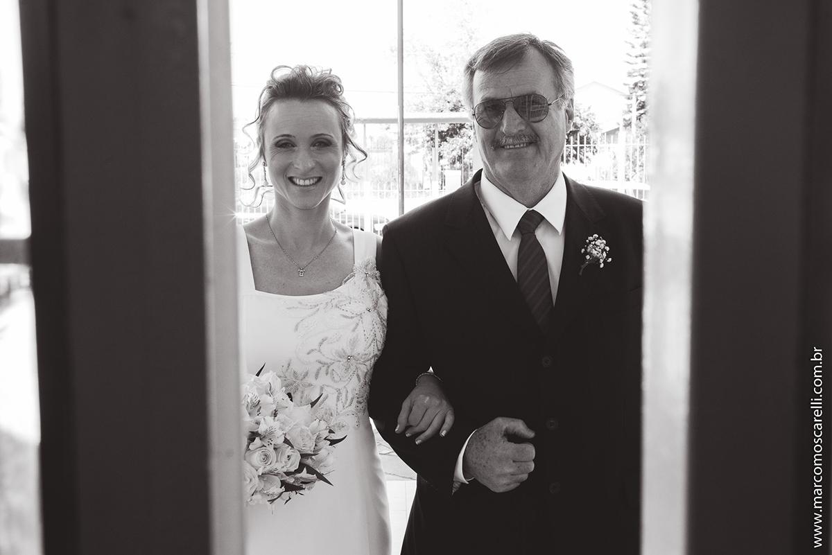 Foto em preto em branco da noiva e do pai na porta de igreja momentos antes do casamento. Foto por Marco Moscarelli