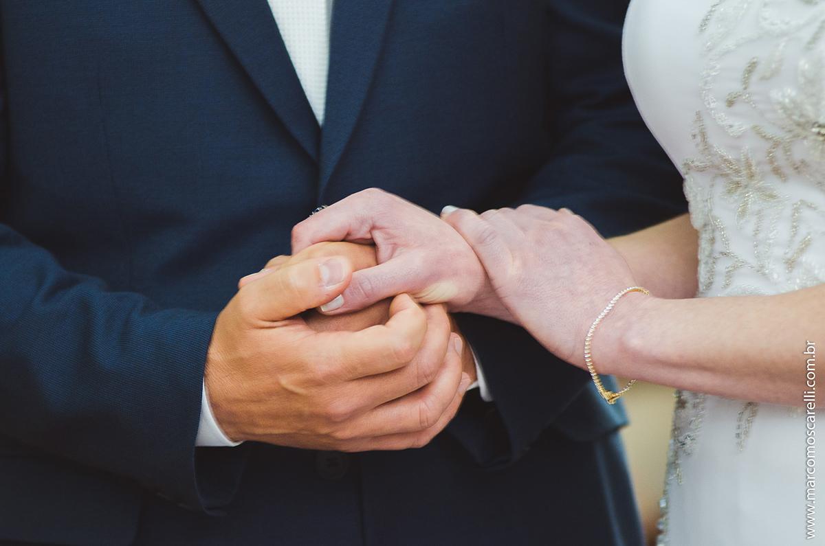Detalhe das mãos dadas dos noivos durante a cerimônia de casamento. Foto por Marco Moscarelli