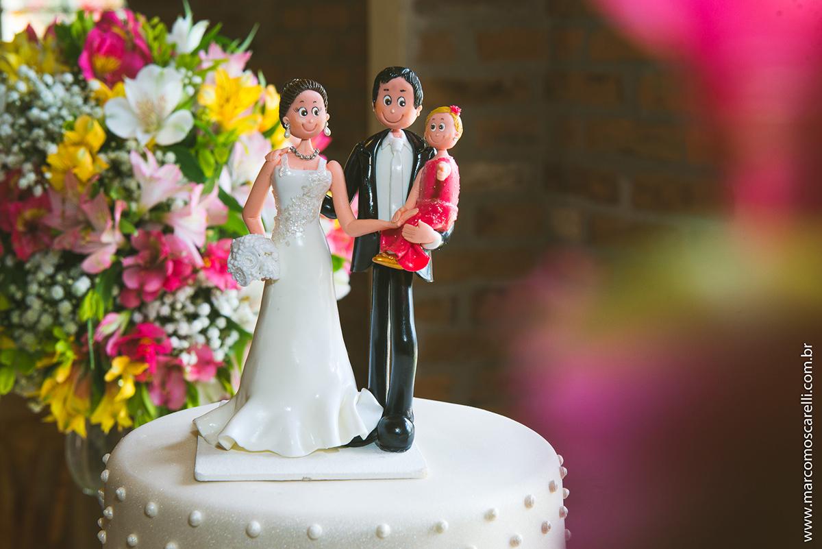 Mesa do bolo linda decorada com flores, does e um lindo casal de noivos no topo do bolo. Foto por Marco Moscarelli
