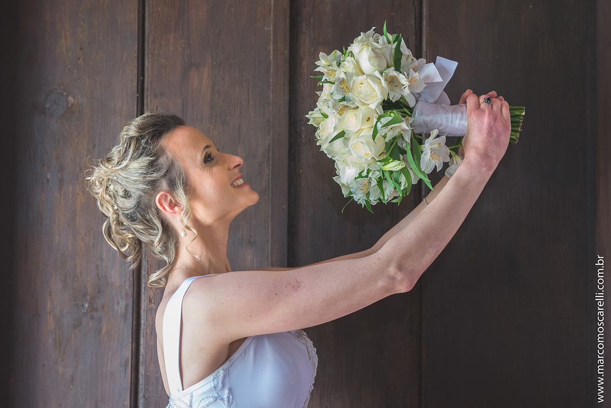 Noiva posando para foto erguendo ao alto seu buqye de noiva com um lindo fundo marrom. Foto por Marco Moscarelli