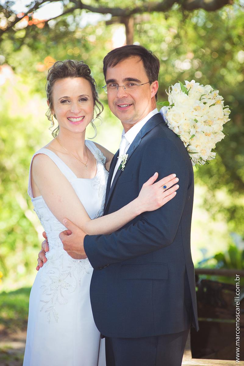Noivos lindos e sorridentes em seu ensaioi após o casamento, posando ao pé de uma linda figueira. Foto por Marco Moscarell