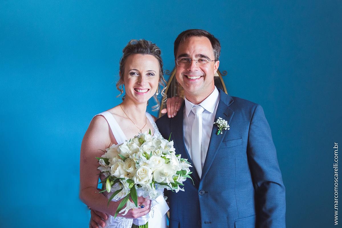 Casal de novos posando para o ensaio pós casamento em uma sala antiga com um lindo fundo azul. Foto por Marco Moscarelli