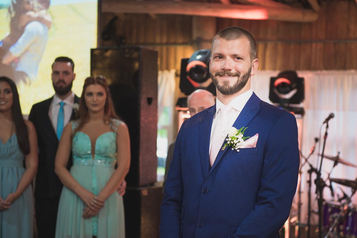 Noivo sorrindo ancioso a espera da noiva no altar. Foto Marco Moscarelli. Casamento Clube Caça e Pesca Pelotas