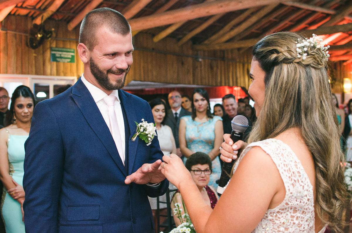 Noiva colocando a aliança no dedo do noivo sorridente. Foto Marco Moscarelli. Casamento Clube Caça e Pesca Pelotas