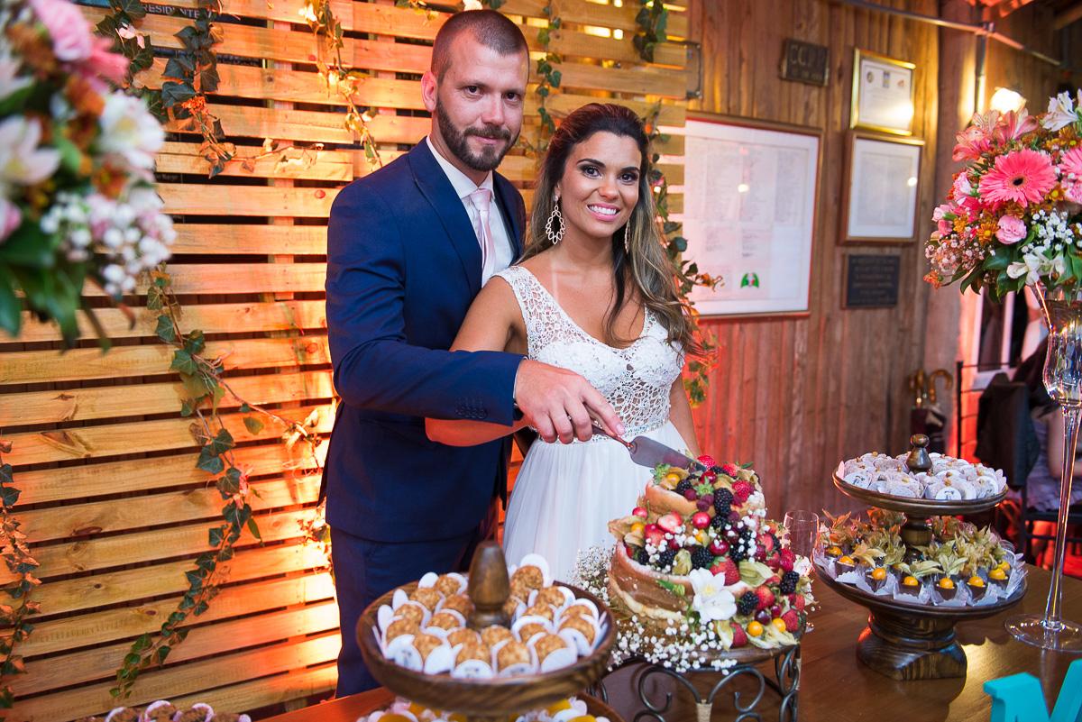 Noivos cortando o bolo do casamento. Foto Marco Moscarelli. Casamento Clube Caça e Pesca Pelotas