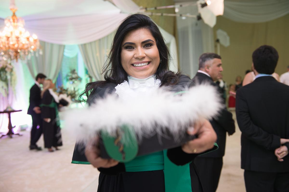Formanda do curso de Medicina segurando a sua toga com um belo sorriso. Foto - Marco Moscarelli
