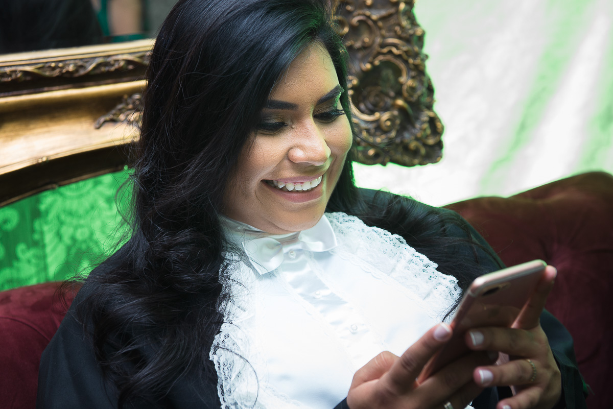 Formanda do curso de medicina sorrindo unsado o celular. Foto - Marco Moscarelli