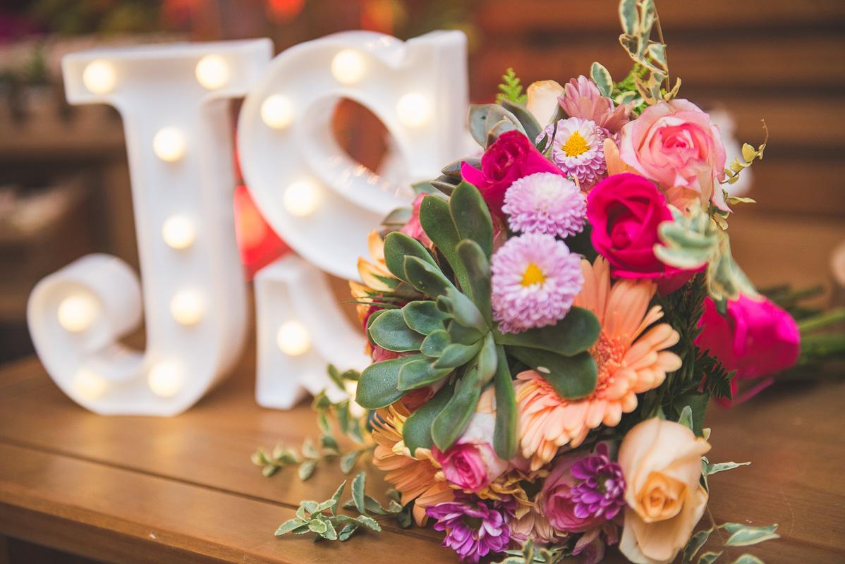 Fotografia em detalhe do buque da noiva com as iniciais do casal de noivos. Foto por Marco Moscarelli Fotógrafo