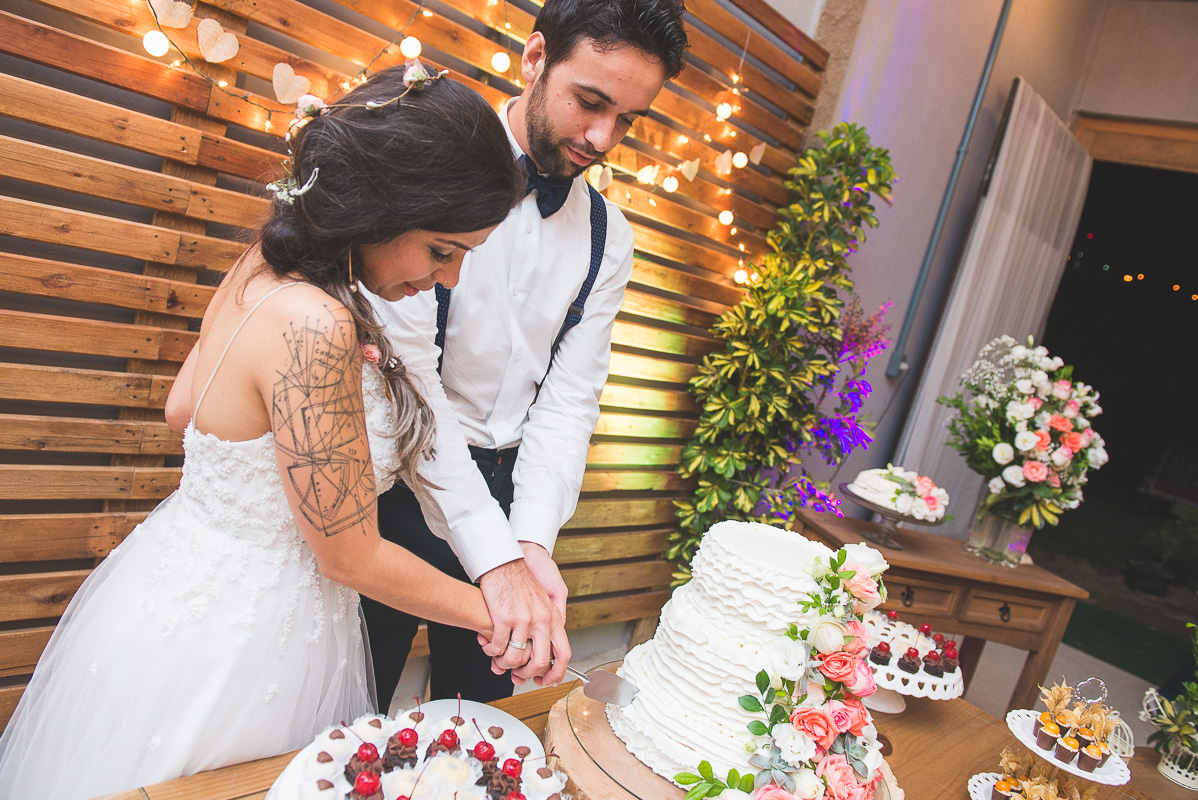 Casal de noivos corantando o bolo de casamento após a cerimônia de casamento. Foto por Marco Moscarelli Fotografo