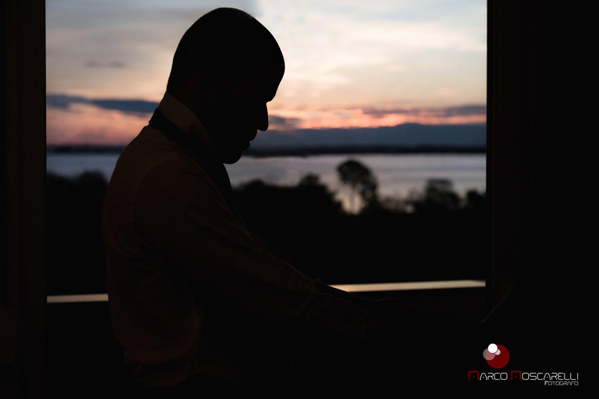 Making of noivo, contra luz na janela do hotel com Rio Graida ao fundo. Foto por Marco Moscarelli