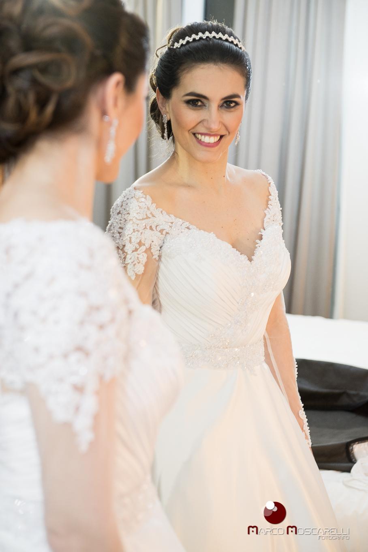 Noiva admirando seu vestido de noiva no espelho antes da cerimonia de casamento. Foto por Marco Moscarelli