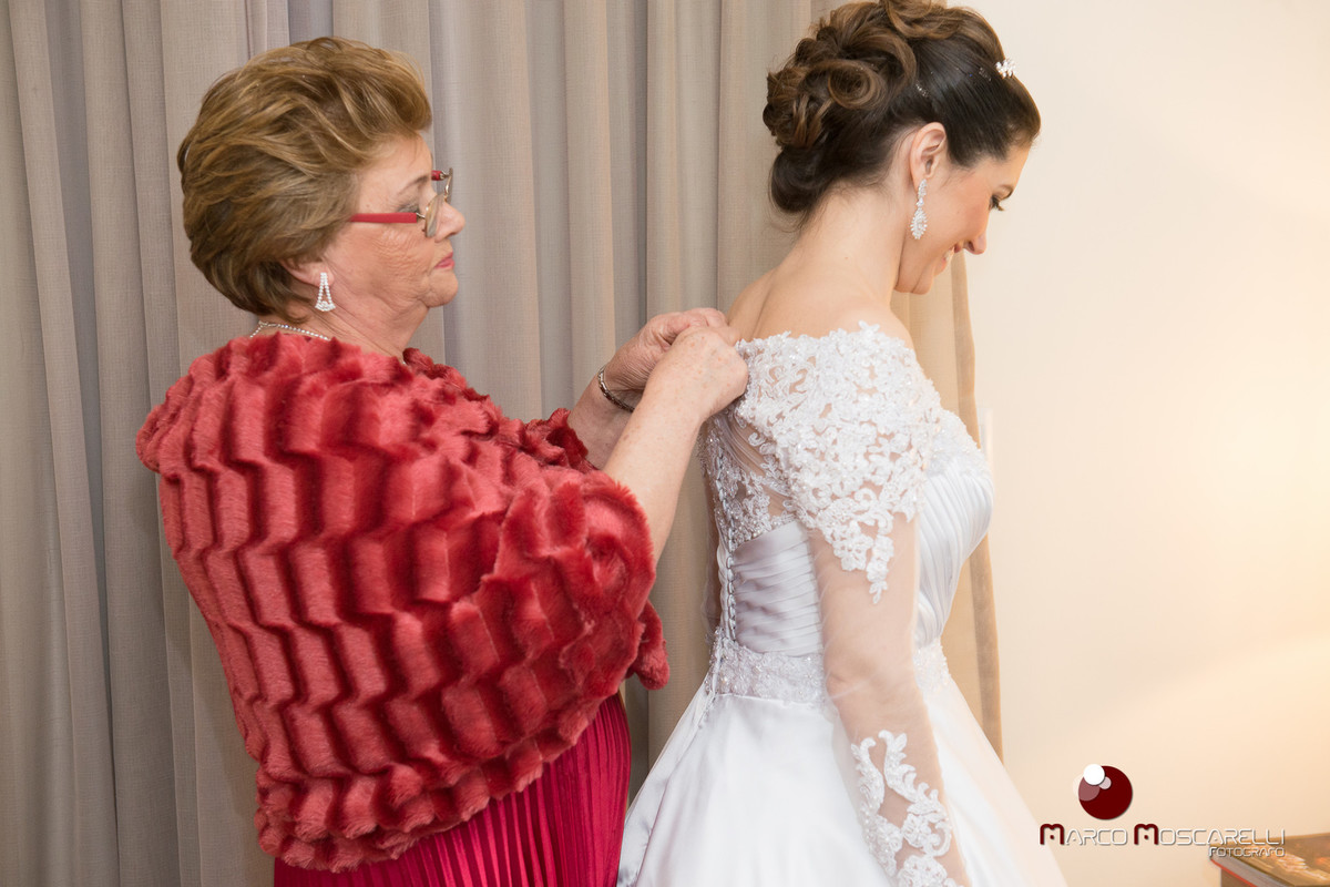 Mãe da noiva abotoando o vestido de noiva momentos antes do casamento. Foto POr Marco Moscarelli