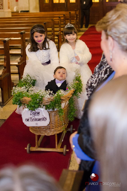 Pagem e aisa entrando na igreja carregando as alianças de casamento. Foto por Marco MOscarelli