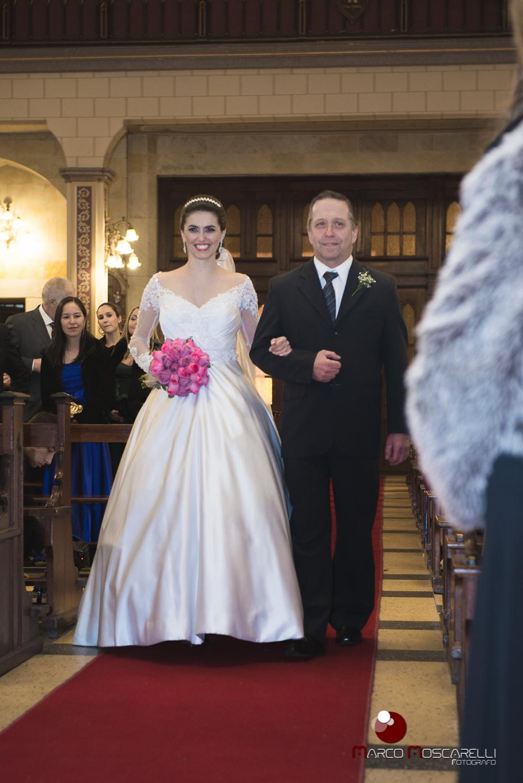 Momento da entrada da noiva na igreja com lindo sorriso no rosto. Foto por Marco Moscarelli