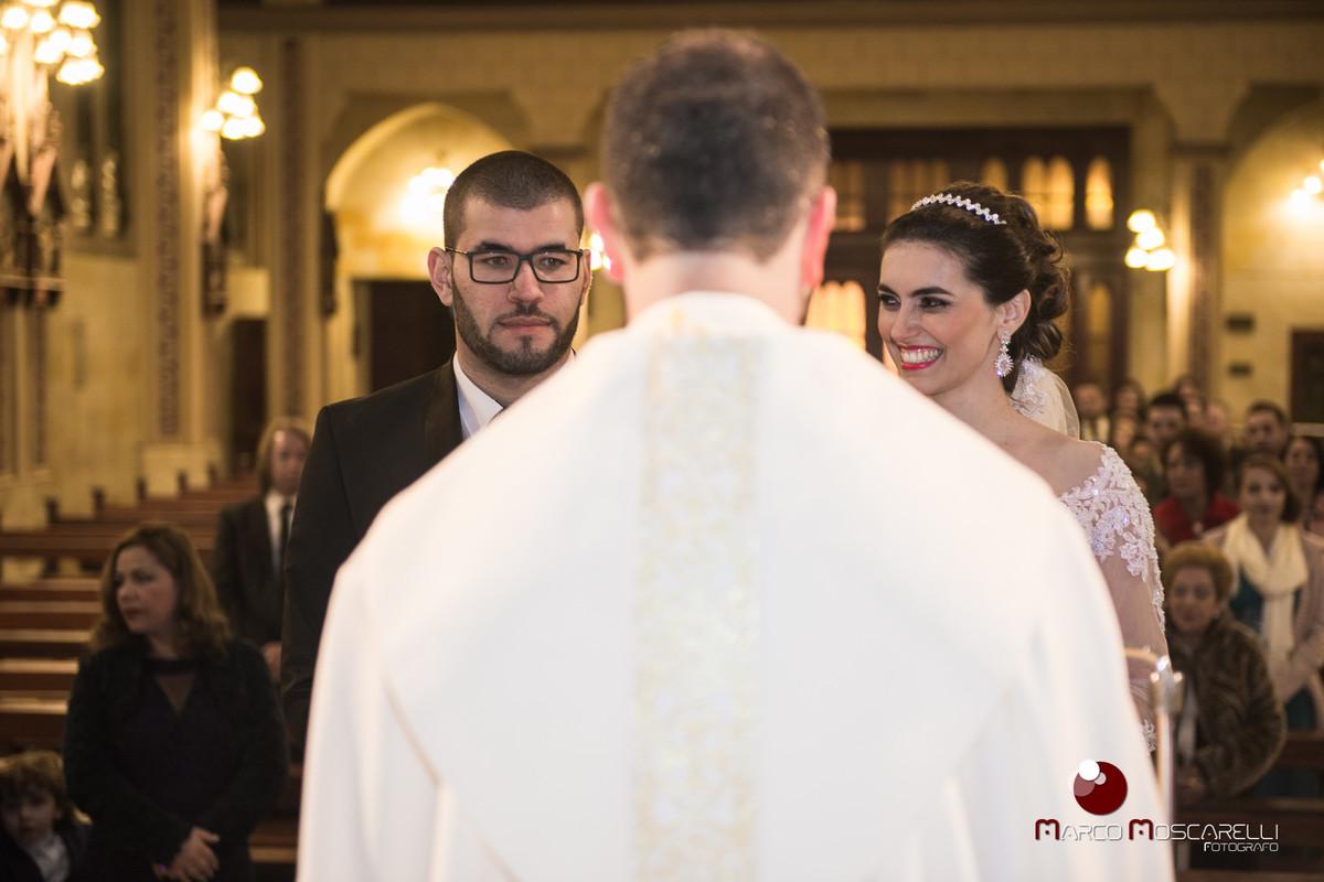 Noiva sorrindo para o noivo no altar da Paroquia São Pedro enquanto padre celebra o casamento. Foto por Marco Moscarelli