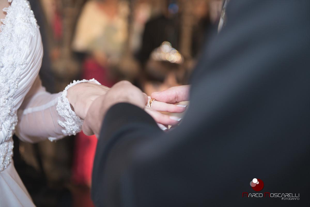 Noivo colocando a aliança de casamento no dedo da noiva. Foto por Marco Moscarelli