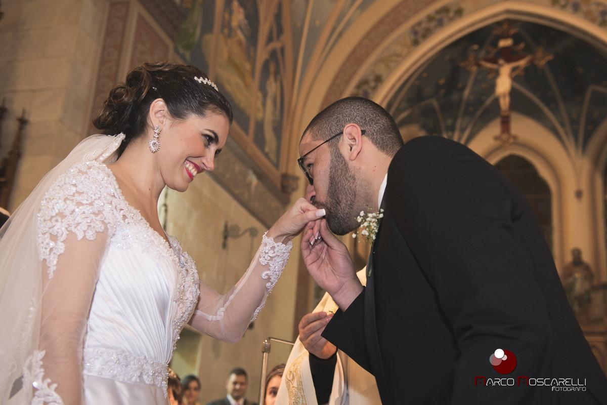 Noivo beja a mão da noiva na hora da troca de alianças de casamento. Foto por Marco Moscarelli