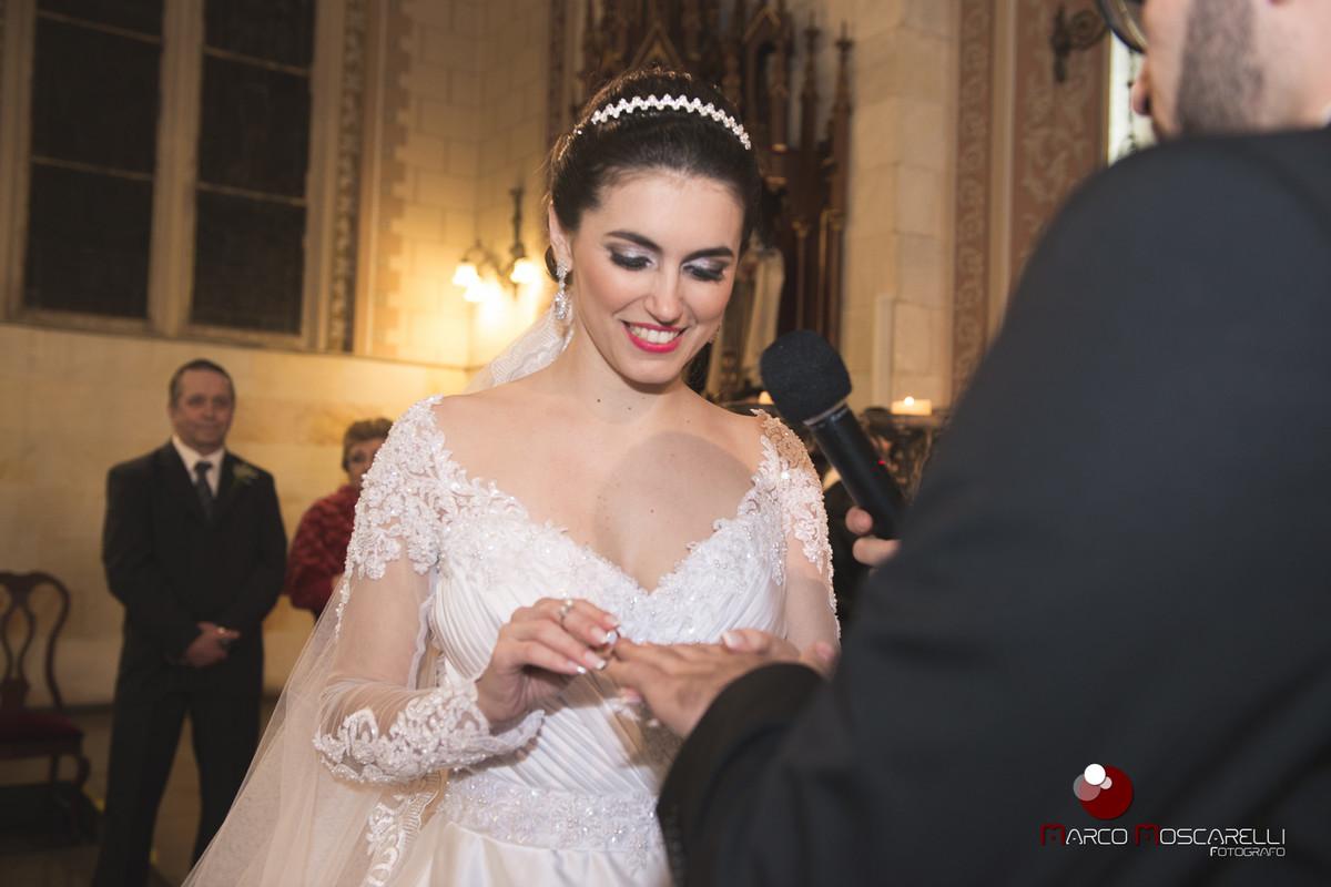 Noiva colocando a aliança no dedo do noivo durante a celebração do casamento. Foto por Marco Moscarelli