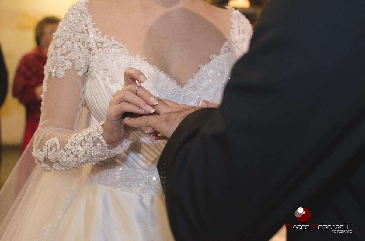 Linda noiva colocando a aliança de casamento no dedo do noivo na cerimonia de casamento