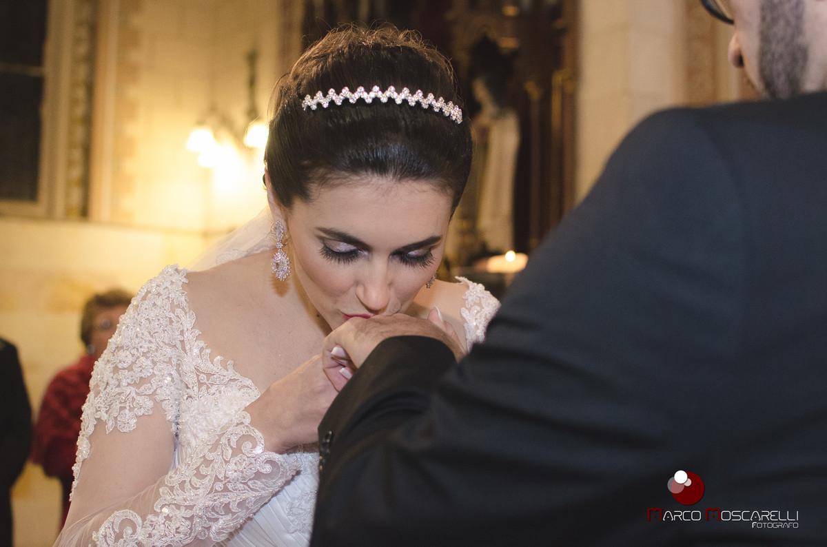 Noiva beijando a aliança do noivo durante a celebração do casamento. Foto por Marco Moscarelli