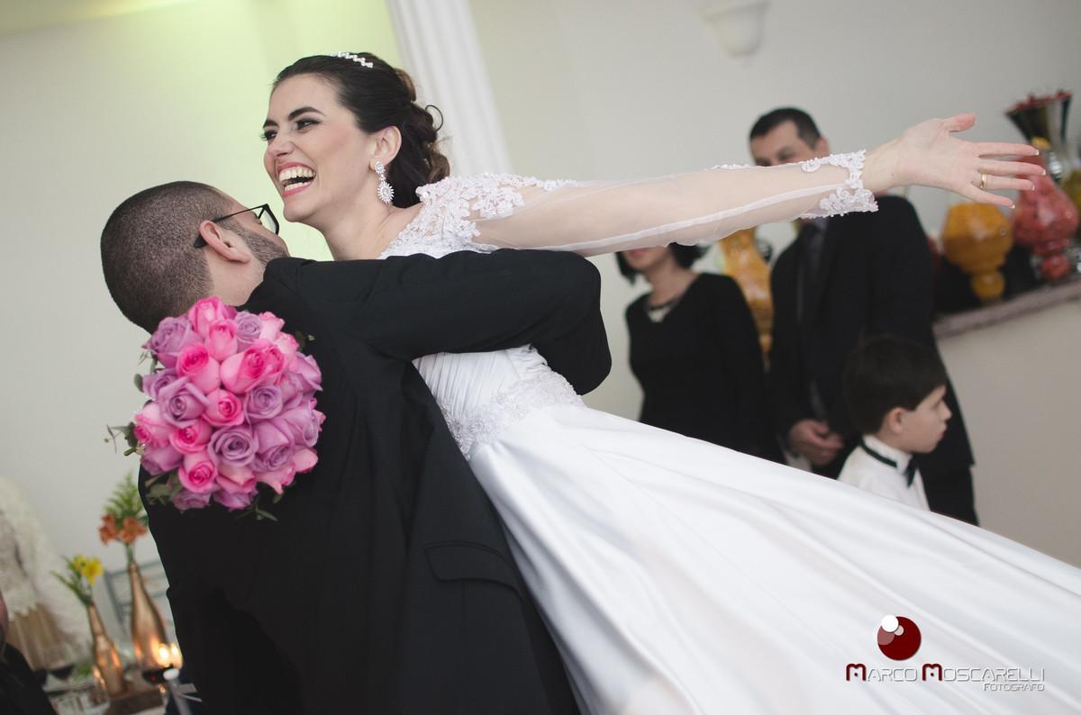 Noiva voando nos braços do noivo durante recepção de casamento.