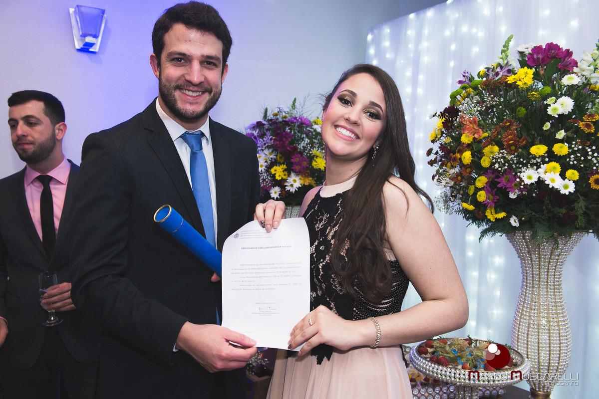 Formanda com lindo sorriso posando junto a convidado, com seu diploma de formartura. Foto por Marco Moscarelli