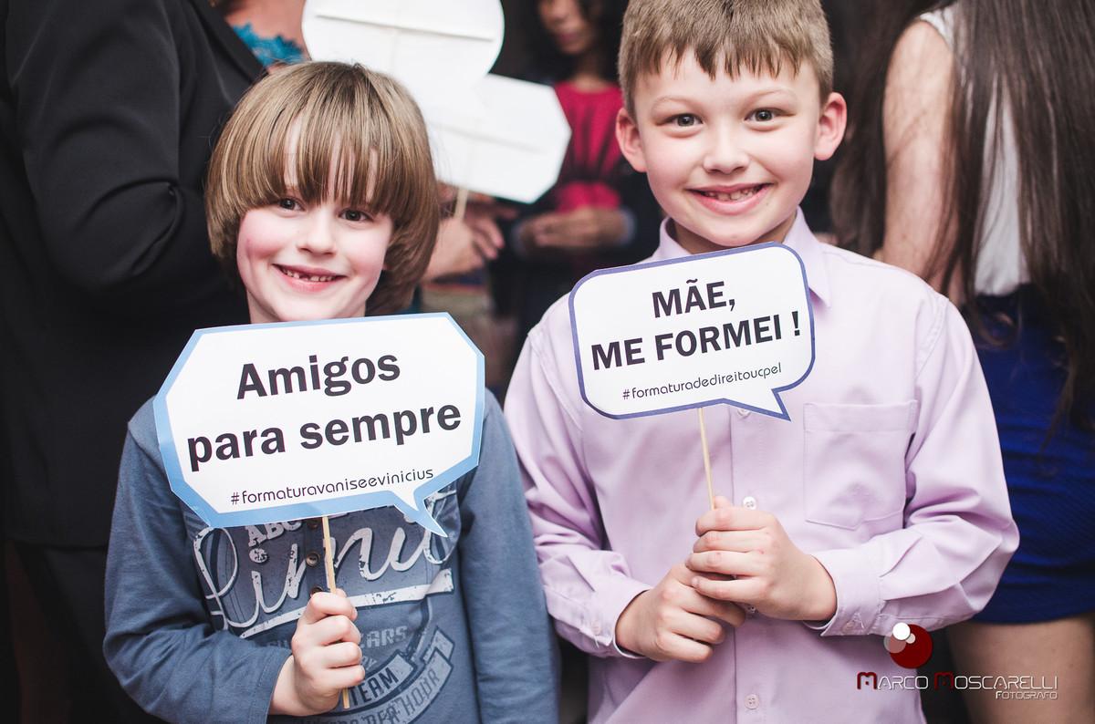 Crianças posando para foto com placas decorativas para o baile dos formandos. Foto por Marco Moscarelli