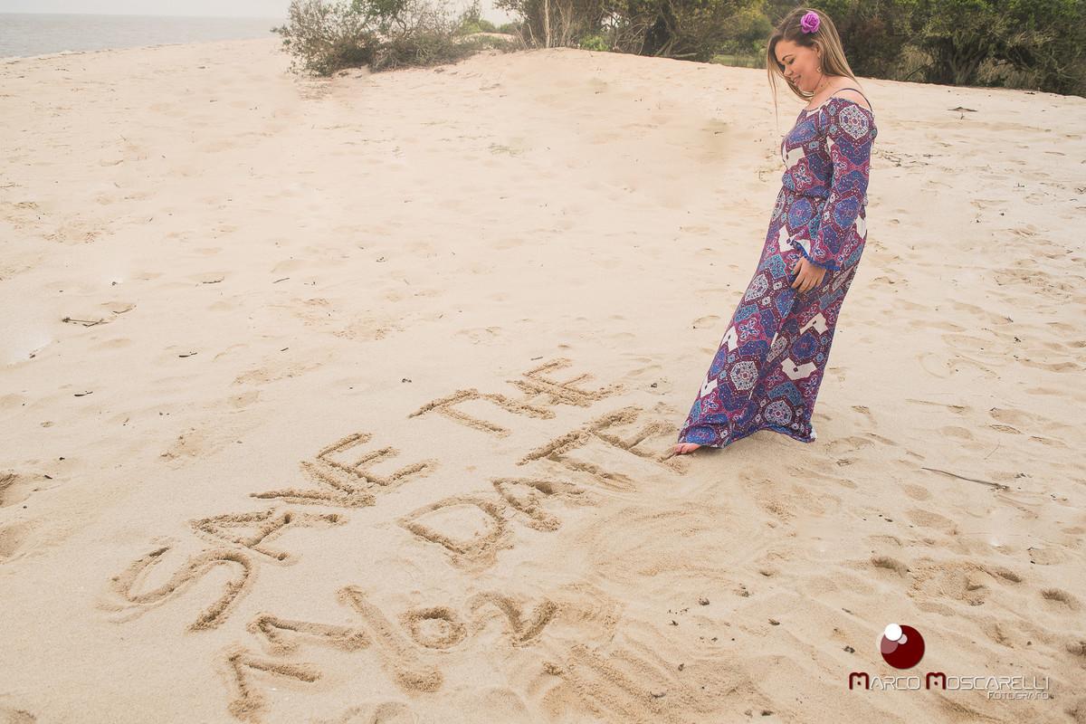 Ensaio da formanda na praia da Ilha da Feitoria, formanda escrevendo save the date na areaia. Foto por Marco Moscarelli