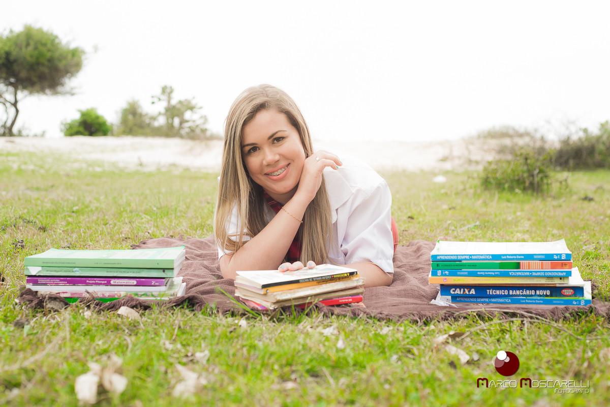 Ensaio da formanda Andressa Bastos na ilha da Feitoria. Formanda debruçada em uma pilha de livros em um lindo gramado verde. Foto por Marco Moscarelli.